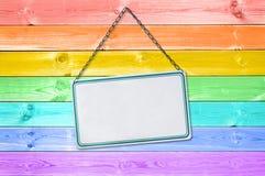 Tecknet för metallplattan som hänger på en pastellfärgad färgrik regnbåge, målade trä royaltyfri foto