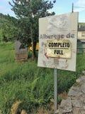Tecknet som indikerar den kommande alberguen på den Camino de Santiago slingan, är fullt, en gemensam händelse i sommarmånaderna Royaltyfri Fotografi