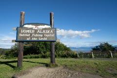Tecknet välkomnar besökare till Homer Alaska på en solig sommardag royaltyfri foto
