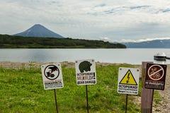 Tecknet varnar av faran av möteturister med björnar på bakgrund av Kurile den sjö- och Ilyinsky vulkan Royaltyfria Bilder