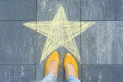 Teckning av färgpennor på asfalten - stjärna och fot av kvinnan royaltyfria foton