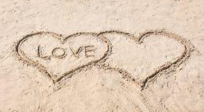 Teckning av hjärtor med ordet FÖRÄLSKELSE på sand Arkivbild