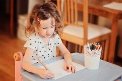 Teckning för förskolebarnbarnflicka med hemmastadda blyertspennor Arkivfoto
