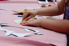 Teckning för litet barn med färgpennor på tabellen Royaltyfria Foton