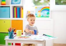 Teckning för litet barn på papperet i rum royaltyfri bild