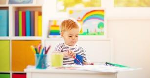 Teckning för litet barn på papperet i rum arkivfoto
