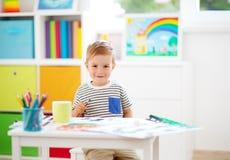 Teckning för litet barn på papperet i rum arkivbilder