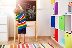 Teckning för litet barn på svart tavla fotografering för bildbyråer
