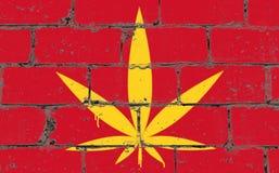 Teckning för sprej för grafittigatakonst på stencilen Cannabisblad på tegelstenväggen med flaggan Vietnam arkivfoto