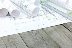 Teckningar för golvplan med ritningrullar och andenivån uppvaktar på Arkivfoto