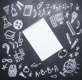 Teckningar på den svart tavlan på det nya studieåret, nedgång, skolatillförsel som dras runt om en anteckningsbok med blyertspenn arkivfoto