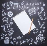Teckningar på den svart tavlan på det nya studieåret, nedgången, skolatillförsel som dras runt om en anteckningsbok med en blyert Royaltyfri Foto