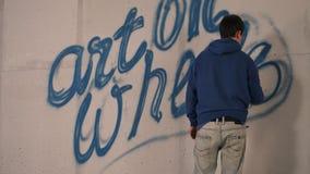 Teckningsgrafitti för ung man på en vägg med en sprejcan Royaltyfri Bild