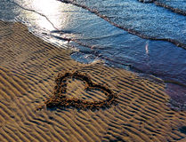 Teckningshjärta på sanden på stranden Arkivfoto