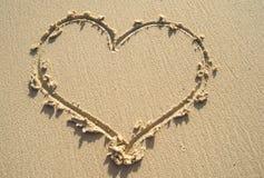 Teckningshjärta på sandstranden. Arkivbilder