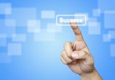 A tecla do sucesso da imprensa da mão no azul Fotografia de Stock Royalty Free