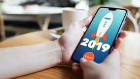 tecla 'Iniciar C?pias' de Rocket de 2019 anos na tela do telefone celular Conceito do neg?cio imagens de stock