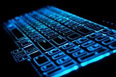 Teclado azul de la computadora portátil del ordenador que brilla intensamente Foto de archivo libre de regalías