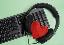 teclado com fones de ouvido com um coração vermelho no verde do fundo Fotos de Stock Royalty Free