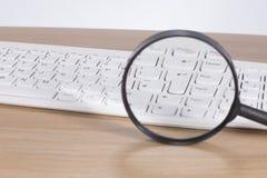 Teclado de computador ampliado através de uma lente de aumento Fotografia de Stock