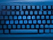 Teclado de computador com Feliz Natal da rotulação nos botões cobertos com a neve iluminada pela luz de néon azul Imagem de Stock