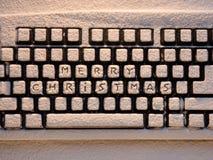 Teclado de computador com Feliz Natal das palavras nos botões cobertos com a neve Fotografia de Stock
