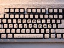 Teclado de computador com Feliz Natal do texto nos botões cobertos com a neve branca Imagens de Stock Royalty Free