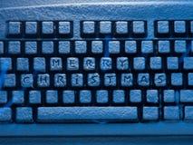 Teclado de computador com Feliz Natal do texto nos botões cobertos com a neve iluminada pela luz de néon azul Fotos de Stock Royalty Free