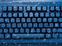 Teclado de computador com Feliz Natal do texto nos botões cobertos com a neve iluminada pela luz de néon e pela queda de neve azu Fotografia de Stock