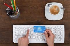 Teclado de computador de Person With Credit Card Using fotografia de stock royalty free