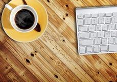 Teclado de computador e um filhote do café na tabela Fotos de Stock Royalty Free
