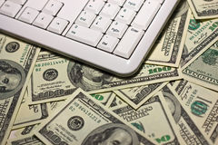 Teclado de computador no fundo de $100 notas de banco Fotografia de Stock Royalty Free