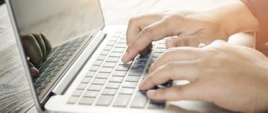 Teclado de dactilografia da mão no portátil imagem de stock