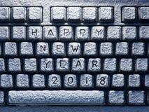 Teclado de escritorio cubierto con la nieve blanca con la Feliz Año Nuevo 2018 del título Foto de archivo libre de regalías
