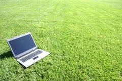 Teclado de la computadora portátil en un campo verde Fotos de archivo libres de regalías
