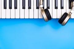 Teclado de la música con el auricular de oro para el espacio azul de la copia Imagen de archivo libre de regalías