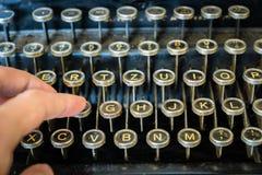 Teclado de máquina de escrever velho com os dedos que datilografam o close-up imagens de stock