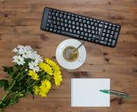 Teclado de ordenador, café de la taza y flor Imagen de archivo