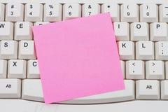 Teclado de ordenador con una nota pegajosa en blanco rosada Imagen de archivo