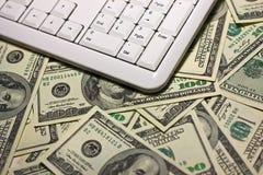 Teclado de ordenador en el fondo de $100 billetes de banco Fotografía de archivo libre de regalías