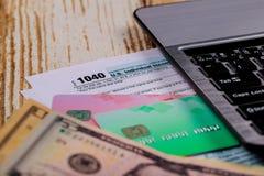 Teclado de ordenador federal de 1040 formas del impuesto y dólares americanos imagen de archivo