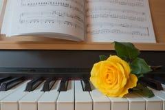 Teclado de piano con el libro de música y la rosa del amarillo Imagen de archivo