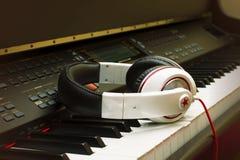 Teclado de piano y auriculares Fotografía de archivo