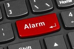 Teclado del cuaderno del ordenador con llave de la alarma Imagenes de archivo