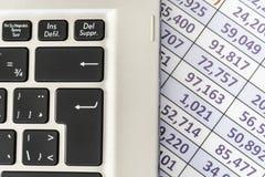 Teclado del ordenador portátil con la hoja de cálculo en el fondo foto de archivo libre de regalías