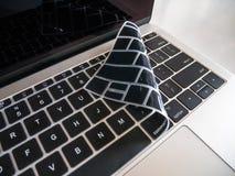 Teclado del ordenador portátil protegido con la cubierta del protector del teclado fotos de archivo