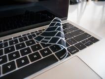 Teclado del ordenador portátil protegido con la cubierta del protector del teclado foto de archivo libre de regalías