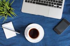 Teclado del ordenador portátil, taza blanca de té en el platillo, libreta, pluma y planta verde en la esquina en fondo arrugado a Fotografía de archivo