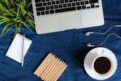 Teclado del ordenador portátil, taza blanca de té en el platillo, libreta, pluma y planta verde en la esquina en fondo arrugado a Fotografía de archivo libre de regalías