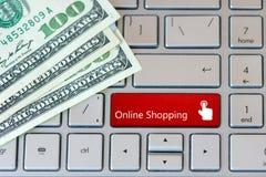 Teclado do portátil com cédulas do dólar e o botão vermelho - compra em linha foto de stock royalty free